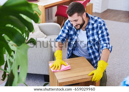 Mid shot of good-looking bachelor in gloves mopping coffee table #659029960