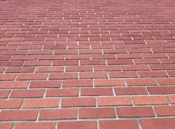 Mid-20th century old tall red brick wall on cloudy afternoon