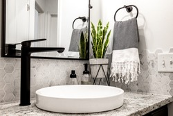 Midcentury modern bathroom with matte black faucet and white sink