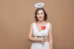 Middle agaed angel elegant brunette woman in white dress with nimbus on head holding red heart sticker and looking at camera with smile. Studio shot, indoor, isolated on light brown background
