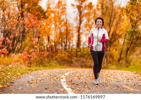 Middle age active and healthy Asian woman exercising weight loss body workout jogging running in park path autumn forest. Middle aged lifestyle. Lady in her 50s.