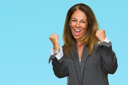 Middle age adult woman wearing oversize boyfriend jacket over isolated background very happy and excited doing winner gesture with arms raised, smiling and screaming for success. Celebration concept.