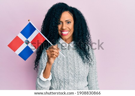 Middle age african american woman holding dominican republic flag looking positive and happy standing and smiling with a confident smile showing teeth  Foto stock ©