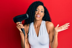 Middle age african american woman holding hair dryer celebrating achievement with happy smile and winner expression with raised hand