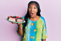 Middle age african american woman holding plate with cake slices scared and amazed with open mouth for surprise, disbelief face