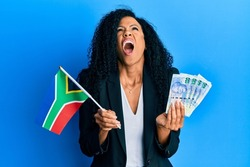Middle age african american woman holding south african flag and rands angry and mad screaming frustrated and furious, shouting with anger looking up.