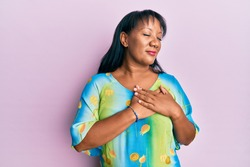 Middle age african american woman wearing casual clothes smiling with hands on chest, eyes closed with grateful gesture on face. health concept.