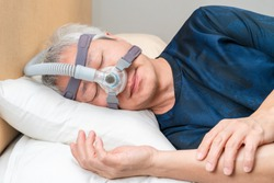 Middle age Asian man wearing CPAP headgear during his sleep