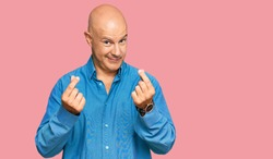 Middle age bald man wearing casual clothes doing money gesture with hands, asking for salary payment, millionaire business
