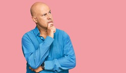 Middle age bald man wearing casual clothes with hand on chin thinking about question, pensive expression. smiling with thoughtful face. doubt concept.
