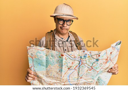 Middle age bald man wearing explorer hat holding map skeptic and nervous, frowning upset because of problem. negative person.  Foto stock ©