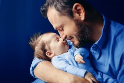 Middle age bearded Caucasian father hugging kissing newborn baby. Man parent holding child. Authentic lifestyle touching tender moment. Dad family life concept. Toned with classic blue 2020 color.