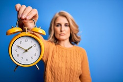 Middle age beautiful blonde woman holding vintage alarm clock over blue background with a confident expression on smart face thinking serious