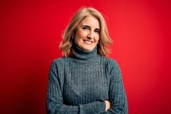 Middle age beautiful blonde woman wearing casual turtleneck sweater over red background happy face smiling with crossed arms looking at the camera. Positive person.