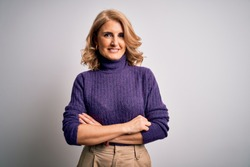 Middle age beautiful blonde woman wearing purple turtleneck sweater over white background happy face smiling with crossed arms looking at the camera. Positive person.