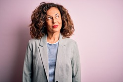 Middle age beautiful businesswoman wearing elegant jacket over isolated pink background smiling looking to the side and staring away thinking.