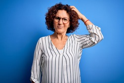 Middle age beautiful curly hair woman wearing casual striped shirt over isolated background confuse and wonder about question. Uncertain with doubt, thinking with hand on head. Pensive concept.