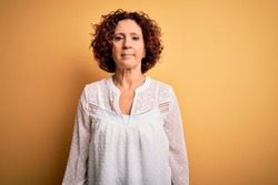 Middle age beautiful curly hair woman wearing casual summer dress over yellow background with serious expression on face. Simple and natural looking at the camera.