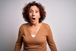 Middle age beautiful curly hair woman wearing casual sweater over isolated white background afraid and shocked with surprise expression, fear and excited face.
