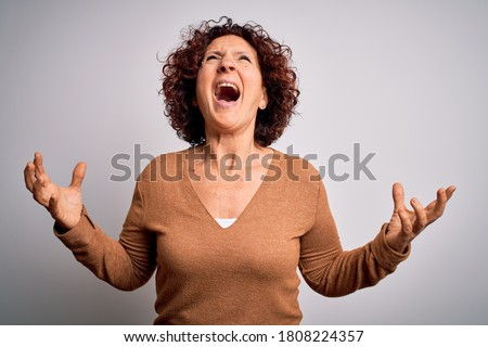 Middle age beautiful curly hair woman wearing casual sweater over isolated white background crazy and mad shouting and yelling with aggressive expression and arms raised. Frustration concept. Stock photo ©