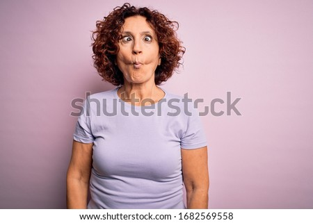 Middle age beautiful curly hair woman wearing casual t-shirt over isolated pink background making fish face with lips, crazy and comical gesture. Funny expression.