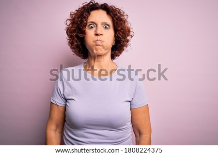 Middle age beautiful curly hair woman wearing casual t-shirt over isolated pink background puffing cheeks with funny face. Mouth inflated with air, crazy expression.