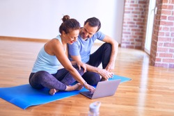 Middle age beautiful sporty couple smiling happy. Sitting on mat with smile on face using laptop at gym