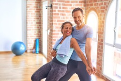 Middle age beautiful sporty couple smiling happy. Standing with smile on face hugging at gym
