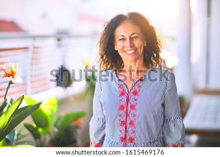 Middle age beautiful woman smiling happy and confident standing with a smile on face at terrace
