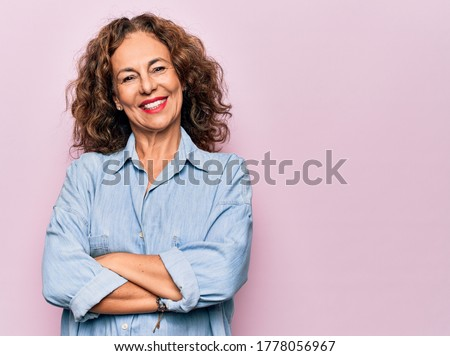 Middle age beautiful woman wearing casual denim shirt standing over pink background happy face smiling with crossed arms looking at the camera. Positive person.