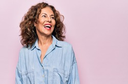 Middle age beautiful woman wearing casual denim shirt standing over pink background looking away to side with smile on face, natural expression. Laughing confident.