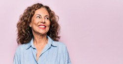Middle age beautiful woman wearing casual denim shirt standing over pink background smiling looking to the side and staring away thinking.