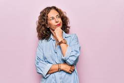 Middle age beautiful woman wearing casual denim shirt standing over pink background with hand on chin thinking about question, pensive expression. Smiling with thoughtful face. Doubt concept.