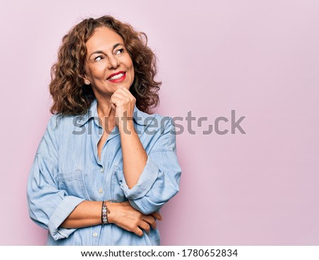 Middle age beautiful woman wearing casual denim shirt standing over pink background with hand on chin thinking about question, pensive expression. Smiling and thoughtful face. Doubt concept.