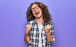 Middle age beautiful woman wearing casual shirt and glasses over isolated purple background celebrating surprised and amazed for success with arms raised and eyes closed