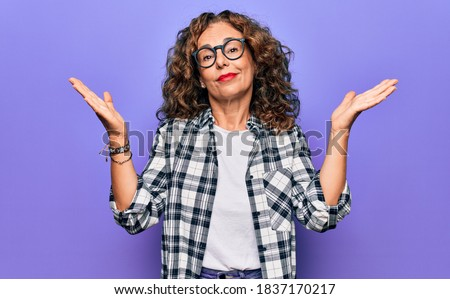 Middle age beautiful woman wearing casual shirt and glasses over isolated purple background clueless and confused with open arms, no idea and doubtful face.