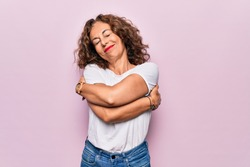 Middle age beautiful woman wearing casual t-shirt standing over isolated pink background hugging oneself happy and positive, smiling confident. Self love and self care