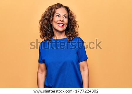 Middle age beautiful woman wearing casual t-shirt standing over isolated yellow background looking to side, relax profile pose with natural face and confident smile.