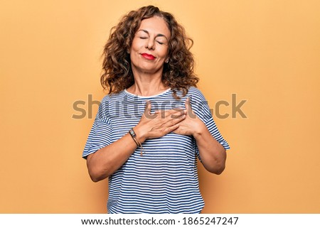 Middle age beautiful woman wearing striped t-shirt standing over isolated yellow background smiling with hands on chest, eyes closed with grateful gesture on face. Health concept. ストックフォト ©