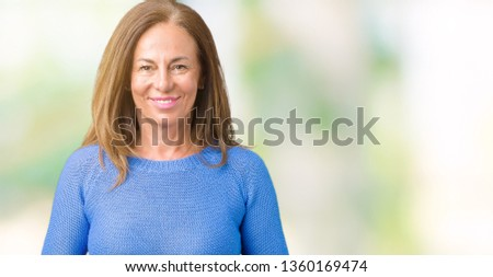 Middle age beautiful woman wearing winter sweater over isolated background Hands together and fingers crossed smiling relaxed and cheerful. Success and optimistic #1360169474