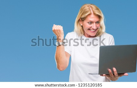 Middle age blonde woman using computer laptop over isolated background screaming proud and celebrating victory and success very excited, cheering emotion