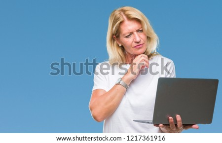 Middle age blonde woman using computer laptop over isolated background serious face thinking about question, very confused idea