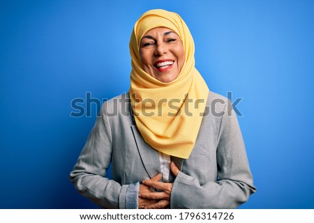 Middle age brunette business woman wearing muslim traditional hijab over blue background smiling and laughing hard out loud because funny crazy joke with hands on body.