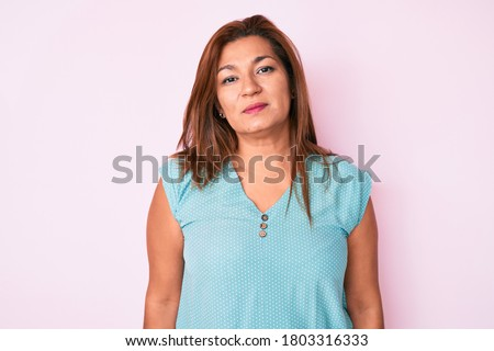 Middle age brunette hispanic woman wearing casual clothes relaxed with serious expression on face. simple and natural looking at the camera.  Foto stock ©