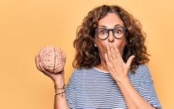 Middle age brunette woman holding brain as mental care and memory health over pink background covering mouth with hand, shocked and afraid for mistake. Surprised expression