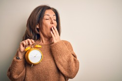 Middle age brunette woman holding clasic alarm clock over isolated background bored yawning tired covering mouth with hand. Restless and sleepiness.
