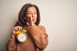 Middle age brunette woman holding clasic alarm clock over isolated background hand on mouth telling secret rumor, whispering malicious talk conversation