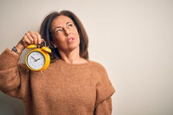 Middle age brunette woman holding clasic alarm clock over isolated background looking sleepy and tired, exhausted for fatigue and hangover, lazy eyes in the morning.