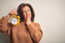 Middle age brunette woman holding clasic alarm clock over isolated background Thinking worried about a question, concerned and nervous with hand on chin