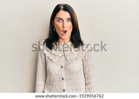 Middle age brunette woman wearing casual clothes afraid and shocked with surprise expression, fear and excited face.  ストックフォト ©